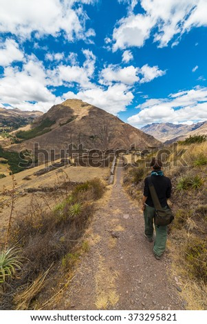 Tourist exploring the Inca Trails leading to the ruins of Pisac, Sacred Valley, major travel destination in Cusco region, Peru. Vacations and adventures in South America. - stock photo