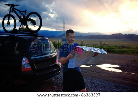 Tourist exploring the map in the evening at sunset - stock photo