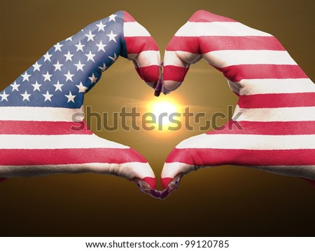 Tourist gesture made by america flag colored hands showing symbol of heart and love during sunrise - stock photo