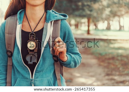 Tourist girl with backpack and compass walking in summer forest - stock photo