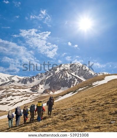 tourist group walking to a mountain pass - stock photo