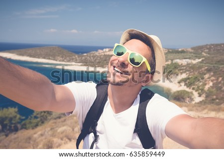 Tourist guy taking selfie at the seaside. Summer, travel and vacation concepts.