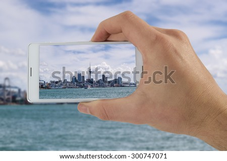 Tourist hand holding smart phone, taking photo of Auckland New Zealand, Devonport