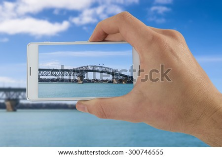 Tourist hand holding smart phone, taking photo of Auckland New Zealand, Harbor bay Bridge - stock photo