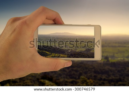 Tourist hand holding smart phone, taking photo of Auckland New Zealand, Mt Maunganui - stock photo