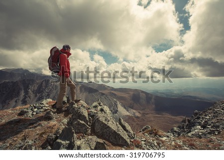 Tourist Hiker man with backpack standing on the edge of Magnificent Mountain Valley. Adventure and Freedom concept - stock photo