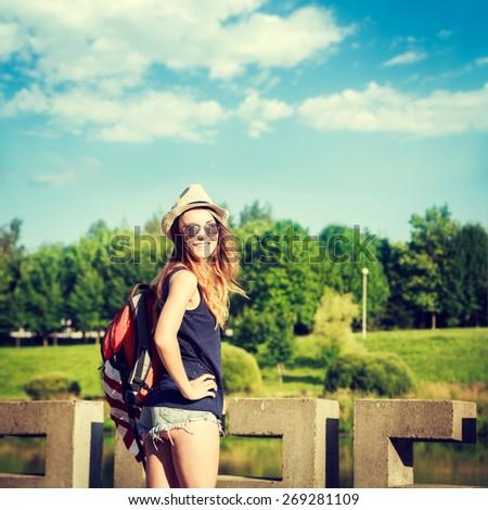 Tourist Hipster Girl Relaxing in the Park. Toned and Filtered Instagram Styled Photo with Copy Space. Vacation and Travel Concept. - stock photo