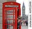 Tourist in a typical red telephone box in London. The Big Ben in background - stock photo