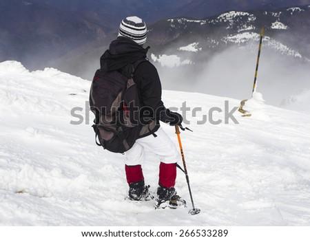 Tourist in a winter mountain - stock photo
