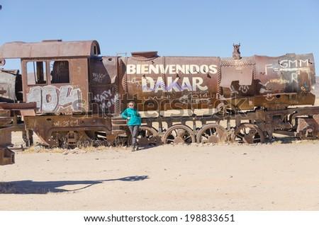 Tourist in Cementerio de trenes (Train Cemetery), Salar de Uyuni, Bolivia - stock photo