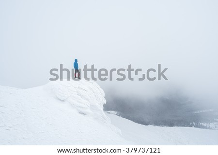 Tourist in mountains. Winter landscape with fog. Man stands on rock and looking over valley. Carpathians, Ukraine, Europe - stock photo