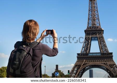tourist in Paris, woman taking photo of Eiffel Tower - stock photo