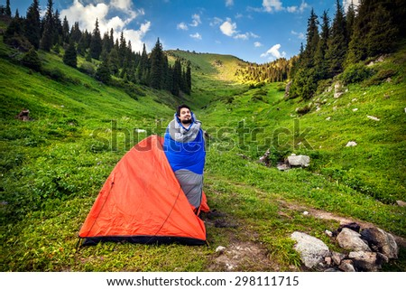 Tourist in sleeping bag near orange tent in the mountains in Kazakhstan, central Asia - stock photo