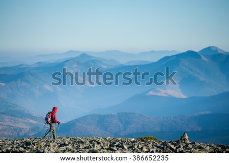 Tourist is walking on the rocky mountain on backpacking trip. Man is wearing red jacket and backpack on. Beautiful mountains on background. Eco tourism and healthy lifestyle concept. Copy space. - stock photo