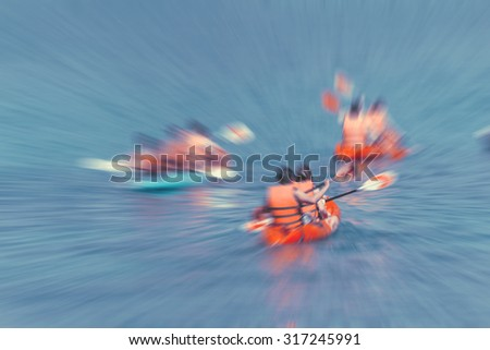 Tourist kayaking in the Thai ocean with radial blur, retro effect - stock photo