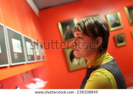 Tourist looking at a picture at the exhibition - stock photo
