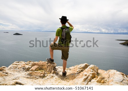 Tourist looking at Lake Titicaca - stock photo