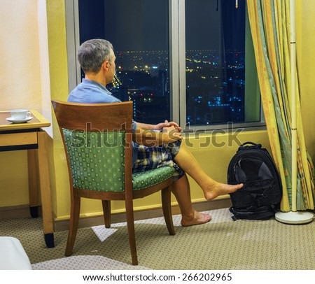 Tourist looks out the window of the hotel rooms at night Bangkok - stock photo
