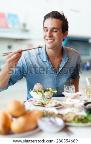Tourist man eating asian food street local cafe, smile using chopstick - stock photo