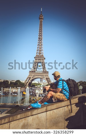 Tourist man in summer clothing over elfel tower. - stock photo
