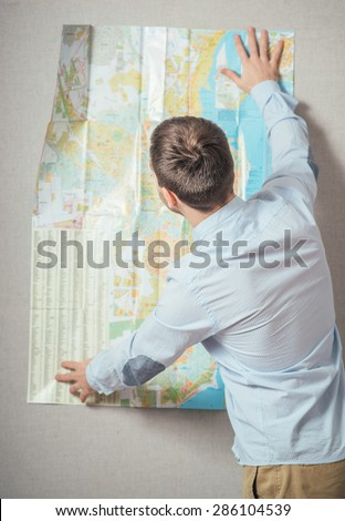 Tourist man looking at map against