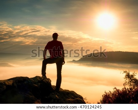 Tourist man on cliff of rock in rock empires park is watching over creamy mist and foggy morning valley to Sun