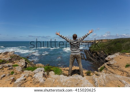 Tourist man on the rocky shore of the sea. He opened his arms with happiness.