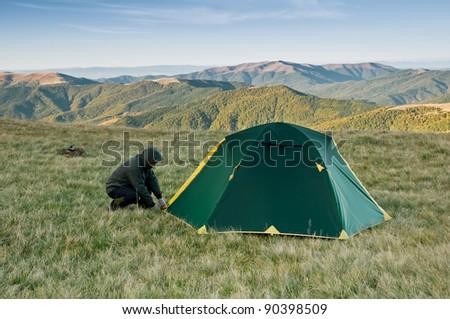 tourist near his tent on mountains - stock photo