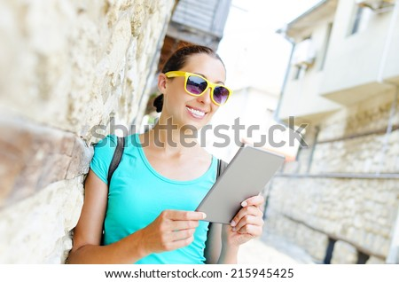 Tourist on the street smiles and holds tablet computer - stock photo