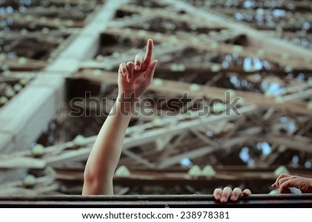 Tourist on top of the Eiffel tower showing the sight  with his hand. Eiffel tower visit and ride. Beautiful Paris sightseeing - stock photo