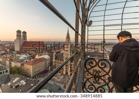Tourist People and Munich City Skyline, Beautiful Vertical Aerial view of Munchen sunset panoramic architecture: Marienplatz, New Town Hall and Frauenkirche at Dusk, Bavaria, Germany - stock photo