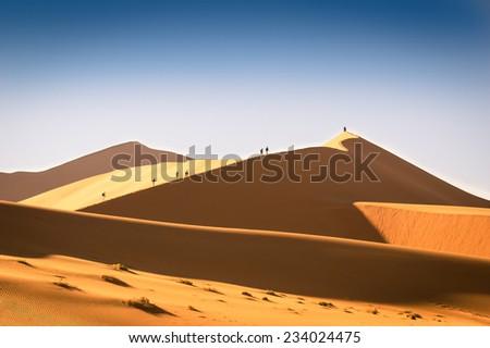 Tourist people hiking on sand dune at Deadvlei near Sossusvlei  - Namibian world famous desert - African nature wonder - stock photo