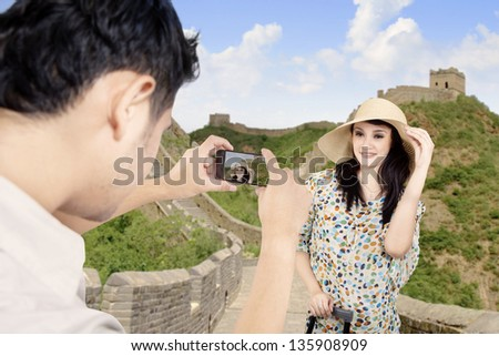 Tourist posing in front of Great Wall in China - stock photo