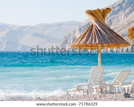 Tourist resort beach - two beach chairs under the shade of a grass umbrella - stock photo