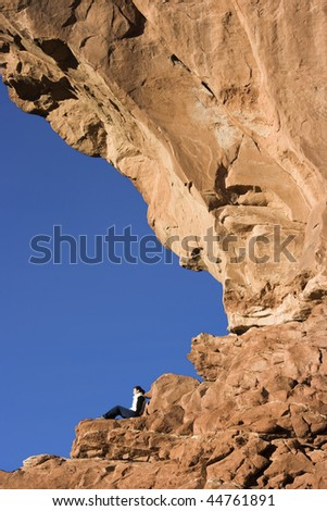 Tourist resting under North Window in Arches National Park. - stock photo