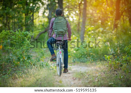 tourist riding bicycle on the forest road