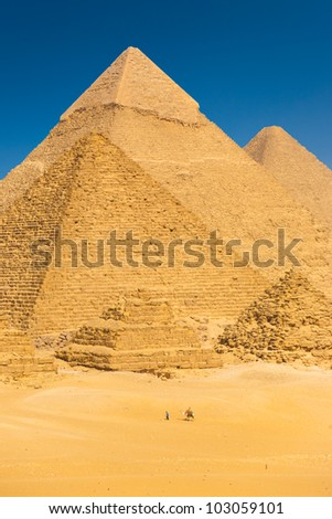 Tourist riding camel passing the imposing base of Great Pyramids in Giza showing relative scale of large size of the structures compared to humans in Cairo, Egypt. Vertical