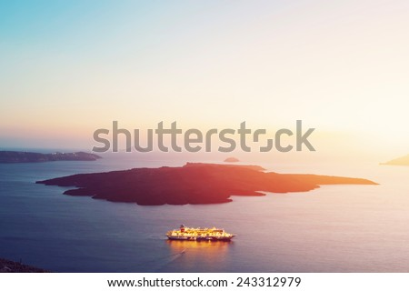 Tourist ship cruiser sailing next to Nea Kameni volcanic island in Santorini, Greece. Sunset - stock photo