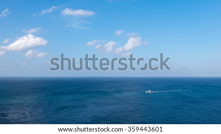 Tourist ship in the sea against blue sky with white clouds.