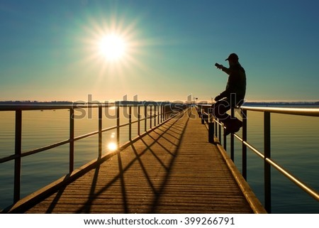 Tourist sit on wharf construction and enjoy morning at sea. Sunny clear blue sky, smooth water level - stock photo