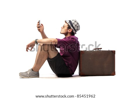 Tourist sitting against a suitcase and using a mobile phone - stock photo