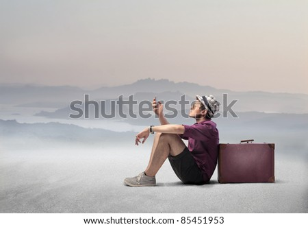 Tourist sitting against a suitcase in a desert and using a mobile phone - stock photo