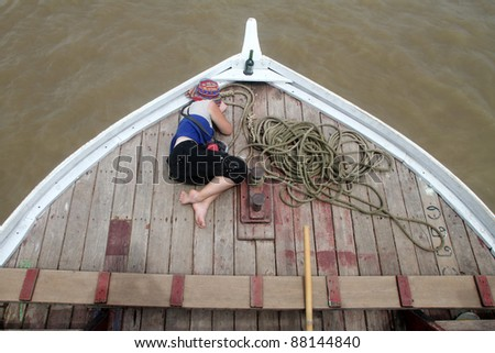 Tourist sleeps on the wooden boat on the way to Mingiun, Myanmar
