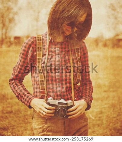 Tourist smiling young woman holding vintage old photo camera in spring outdoor. Vintage image - stock photo
