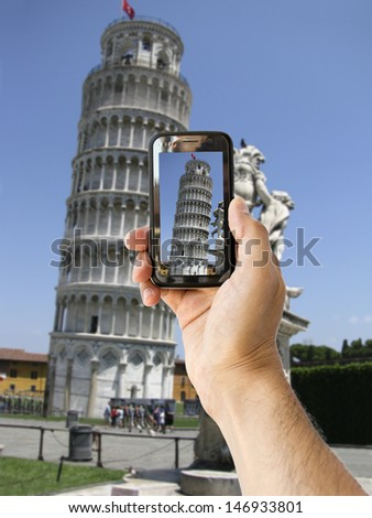 tourist takes a picture with his mobile of  Leaning Tower of Pisa in Italy - stock photo