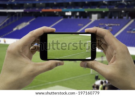 tourist takes a picture with his mobile of the football stadium - stock photo