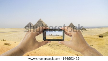 tourist taking a picture with your mobile and the pyramids of Giza in Egypt - stock photo