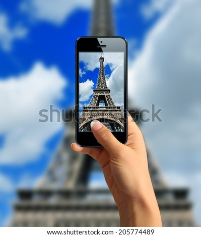 Tourist taking a picture with your mobile phone Eiffel tower - stock photo