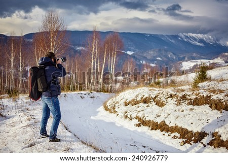 Tourist taking photos of mountains at sunset in a winter evening - stock photo