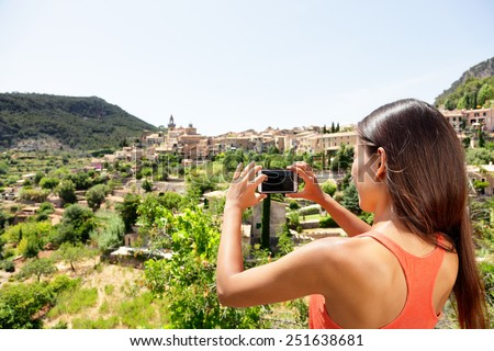 Tourist taking picture of Deia Village in Mallorca. Travel woman hiker using smartphone app to take a landscape photo of the Unesco World Heritage site on Majorca, Balearic Islands, Spain. - stock photo